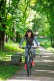 Mujer del ciclista que monta una bicicleta en parque Imagen de archivo libre de regalías