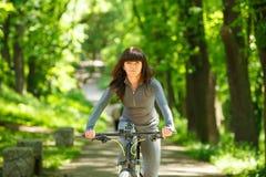 Mujer del ciclista que monta una bicicleta en parque Foto de archivo libre de regalías