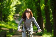 Mujer del ciclista que monta una bicicleta en parque Imagenes de archivo