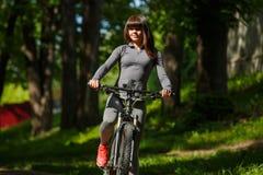 Mujer del ciclista que monta una bicicleta en parque Fotografía de archivo
