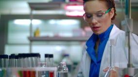 Mujer del científico que mira el teléfono Movimiento en sentido vertical femenino del científico en el teléfono en laboratorio almacen de video