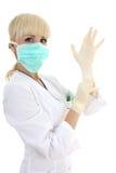 Mujer del cirujano en guantes de la máscara y del caucho sobre blanco Fotos de archivo libres de regalías