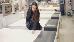 Mujer del cliente que compra nuevos muebles - sofá o sofá en una tienda almacen de metraje de vídeo
