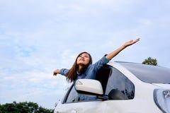 Mujer del coche en el camino en el viaje por carretera que agita la sonrisa feliz Imagen de archivo libre de regalías
