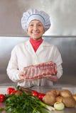Mujer del cocinero con la carne sin procesar Imagen de archivo