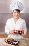 Mujer del cocinero con los rodillos de sushi cocinados Foto de archivo libre de regalías