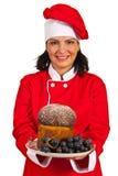 Mujer del cocinero que sostiene la torta de esponja con las uvas Imágenes de archivo libres de regalías