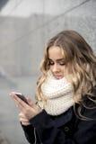 Mujer del comprador que compra en línea en el teléfono elegante en la calle Imagen de archivo libre de regalías