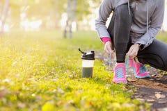 Mujer del corredor del deporte que ata cordones antes de entrenar Maratón Fotografía de archivo