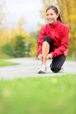 Mujer del corredor que ata los zapatos corrientes Foto de archivo libre de regalías