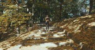 Mujer del corredor que consigue lista para correr y comienzo que corre en los auriculares que llevan que escuchan la música metrajes
