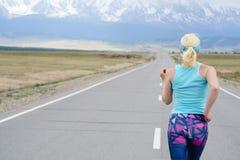 Mujer del corredor que corre en el camino en naturaleza hermosa Traini que activa Imagen de archivo