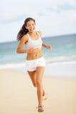 Mujer del corredor que corre en la sonrisa de la playa feliz Fotos de archivo libres de regalías