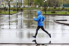 Mujer del corredor que corre en parque en la lluvia Entrenamiento que activa para m Imagen de archivo