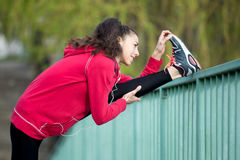Mujer del corredor que hace estiramiento del tendón de la corva después de activar Fotografía de archivo