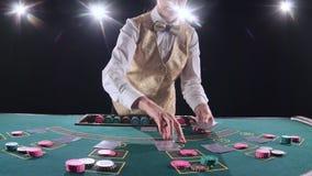 Mujer del crupié del casino que mezcla las tarjetas del póker y que realiza truco con las tarjetas Fondo negro Luz brillante lent metrajes