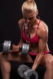 Mujer del culturista de la aptitud con pesas de gimnasia muchacha rubia hermosa con los músculos imagen de archivo libre de regalías