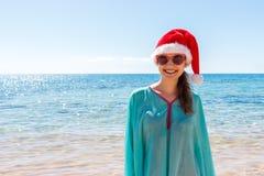 Mujer del día de fiesta en el sombrero de santa que se relaja en la playa del paraíso Vacaciones de la Navidad imagen de archivo