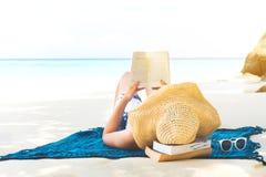 Mujer del día de fiesta de la playa del verano que lee un libro en la playa en tiempo libre foto de archivo