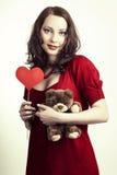Mujer del día de tarjetas del día de San Valentín que sostiene el corazón y el juguete suave en sus manos Imagen de archivo