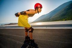 Mujer del deporte con los rodillos en la carretera Foto de archivo libre de regalías
