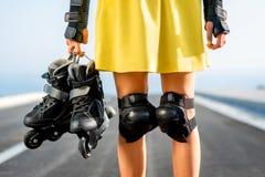 Mujer del deporte con los rodillos en la carretera Foto de archivo