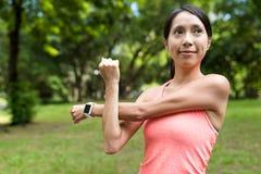 Mujer del deporte que estira el brazo en parque Imagenes de archivo