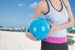 Mujer del deporte que sostiene la pelota de playa con la imagen de la playa en fondo Fotografía de archivo libre de regalías