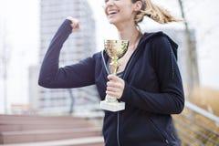 Mujer del deporte que sostiene un trofeo foto de archivo libre de regalías
