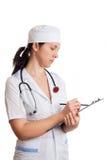 Mujer del doctor con la escritura del estetoscopio en papeles Imagen de archivo libre de regalías