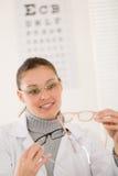 Mujer del doctor del óptico con los vidrios y la carta de ojo Imagen de archivo libre de regalías