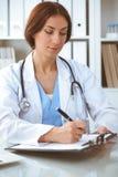 Mujer del doctor en el trabajo El relleno del m?dico encima de expedientes del historial m?dico forma en el escritorio Medicina,  foto de archivo