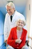 Mujer del doctor Pushing Happy Elderly en silla de ruedas Foto de archivo libre de regalías