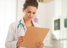 Mujer del doctor que mira en tablero Fotos de archivo