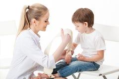 Mujer del doctor y paciente del niño Vendaje de la mano con un vendaje Fondo blanco aislado Fotografía de archivo