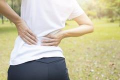 mujer del dolor de espalda en parque, dolor y lesión de espalda como se resuelven o exe fotografía de archivo