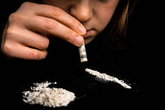 Mujer del drogadicto que esnifa el polvo de la cocaína con el billete de banco rodado imagen de archivo libre de regalías