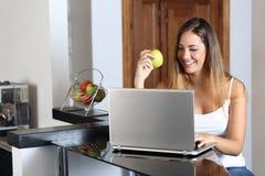 Mujer del empresario que hojea un ordenador portátil y que come en casa Imagen de archivo
