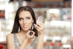 Mujer del encanto con el espejo del lápiz labial y del maquillaje fotografía de archivo libre de regalías
