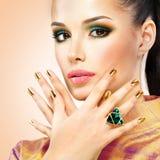 Mujer del encanto con los clavos de oro hermosos y el anillo esmeralda Foto de archivo libre de regalías