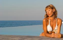 Mujer del encanto en el bikiní blanco en piscina del infinito Foto de archivo libre de regalías