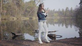 Mujer del encanto en los pantalones, la chaqueta blanca de los vaqueros y las gafas de sol colocándose en el riverbank La muchach metrajes