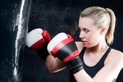 Mujer del entrenamiento del boxeo con el bolso de perforación en gimnasia Imagenes de archivo