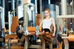 Mujer del entrenamiento del ejercicio de la extensión de la pierna del gimnasio interior imágenes de archivo libres de regalías