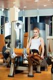 Mujer del entrenamiento del ejercicio de la extensión de la pierna del gimnasio interior foto de archivo libre de regalías
