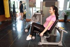 Mujer del entrenamiento del ejercicio de la extensión de la pierna del gimnasio interior Hermoso, prensa fotos de archivo