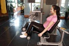 Mujer del entrenamiento del ejercicio de la extensión de la pierna del gimnasio interior Hermoso, prensa foto de archivo libre de regalías