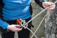 Mujer del escalador en el arnés de seguridad que ata la cuerda en nudo de bolina Foto de archivo