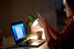 Mujer del estudiante con el ordenador portátil y el smartphone en casa Foto de archivo