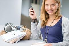 Mujer del estudiante con las notas y el teléfono celular Imagen de archivo libre de regalías